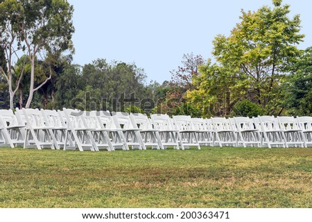 Rows of outdoor white wooden folding chairs on the green grass. Event celebration concept. Park setting, trees and blue sky background.