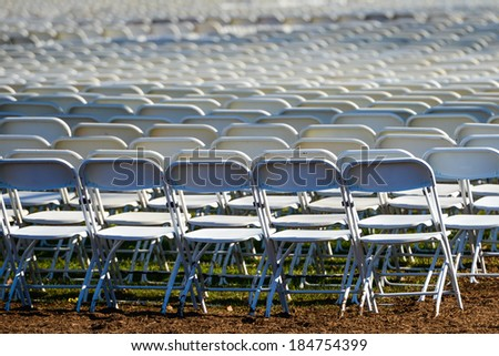 Rows of portable plastic chairs prepared for a open air event