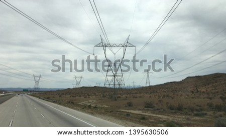 Rows of pylons bearing high tension electric cables crossing freeway and disappearing towards mountains, Apple Valley region, California. Overcast day #1395630506