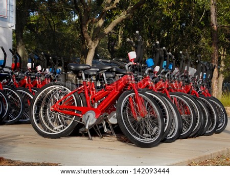 Rows of red bicycles lined up and ready to be rented on a sunny day at a vacation destination.