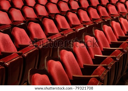 Rows of red velvet theater seats in an old Vaudeville style theater.