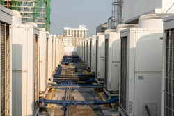 Rows of rooftop HVACs on the roof deck of an office tower. VRF or VRV air conditioner for commercial buildings