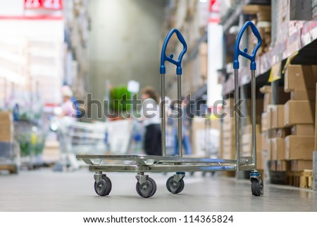 Rows of shelves with boxes and storage carts in modern warehouse