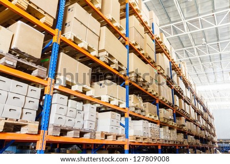Shutterstock Rows of shelves with boxes in factory warehouse