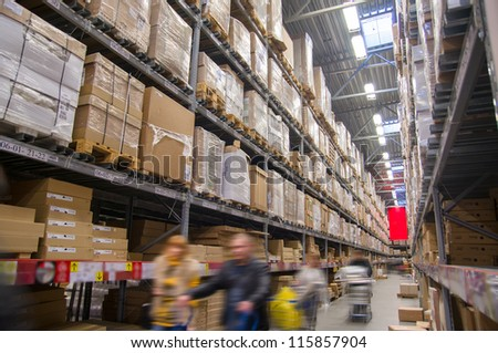 Rows of shelves with boxes in modern warehouse with customers walking