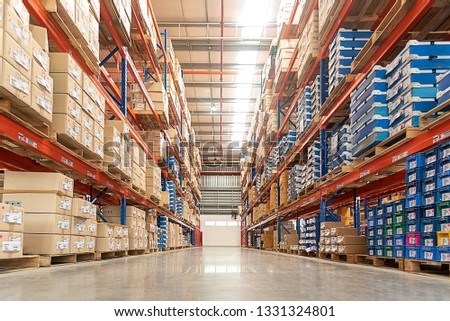Rows of shelves with goods boxes in huge distribution 