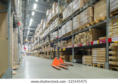 Rows of shelves with huge cardboard boxes and orange storage carts on floor in modern warehouse