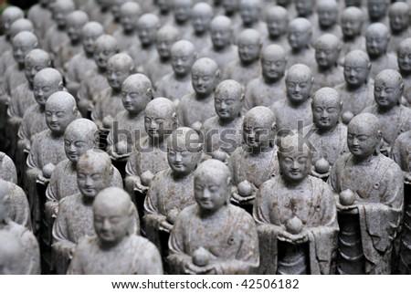 rows of similar japanese jizo sculptures in Hase-Dera temple, Kamakura, Japan; focus on central part