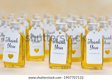 Rows of small twist-cap bottles filled with yellow liquid (oil, honey, bubble bath, massage oil) with thank-you cards attached to the front, with space for message or text ストックフォト ©