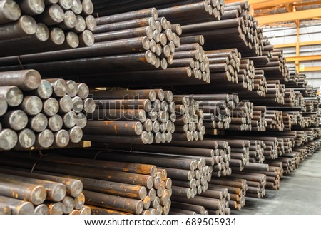 Rows of Steel Round Bar storage and stacking in the warehouse for industrial construction. Shallow focus.