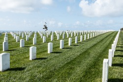 Rows of tombstones with a partly cloudy blue sky at Fort Rosecrans National Cemetery in San Diego, California.