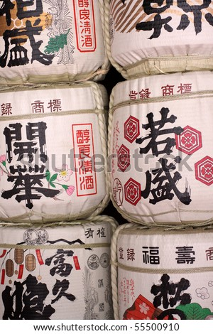 Rows of traditional Japanese sake rice wine barrels with symbols on them