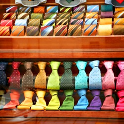 Rows of varicoloured silk neckties in a shop window. Composition of male accessories in different colour and textures.