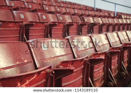 Rows of vintage red painted bleachers receding in the distance