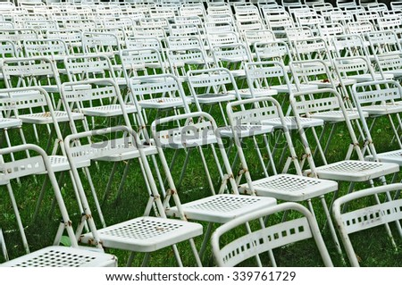 rows of white chairs in an open air theatre of a public park