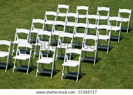 Rows of white empty chairs on a lawn before a wedding or ceremony