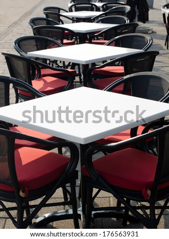 Rows of white empty tables and black wicker chairs in an open air cafeteria. Cafe bar on sunny summer day.