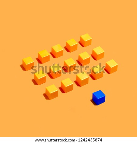 Rows of yellow cubes and blue in front on yellow background. Minimal style. Symbolic concept of leadership, individuality, difference from others