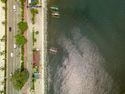Roxas Boulevard and boardwalk. Top view of Manila Bay. A few outrigger boats moored on the breakwater.