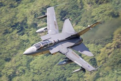 Royal Air Force (RAF) Tornado GR4 strike fighter flying fast  and low level in a mountain valley in Snowdonia North Wales.