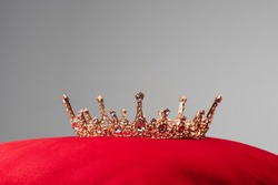 royal crown on red velvet cushion isolated on grey