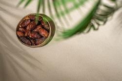 Royal dates fruit in a bowl of coconut on the sand beach under palm branches and leaves shadow.