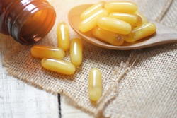 Royal jelly capsules in wooden spoon and sack background / Yellow capsule medicine or supplementary food from nature for health