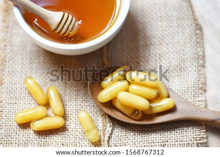 Royal jelly capsules in wooden spoon on sack background and honey in cup / Yellow capsule medicine or supplementary food from nature for health
