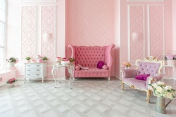 royal sitting room luxury interior of large flat in pink colors with expensive furniture in rich barocco style decorated with flowers in vases.  royal sitting room