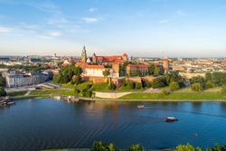 Royal Wawel Cathedral and castle in Krakow, Poland. Aerial view in sunset light. Vistula River, tourist boats, canoes, riverbank with park. promenade and  walking people