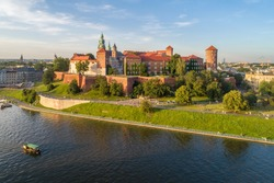 Royal Wawel Cathedral and castle in Krakow, Poland. Aerial view in sunset light. Vistula River, tourist boat, riverbank with park, promenade and  walking people