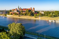 Royal Wawel Cathedral and castle in Krakow, Poland. Aerial view in sunset light. Vistula River, tourist boats, canoes, riverbanks with trees, parks, promenade and  walking people
