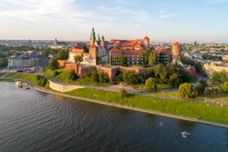 Royal Wawel Cathedral and castle in Krakow, Poland. Aerial view in sunset light. Vistula River with people on stand up puddles, riverbank with park. promenade and  walking people