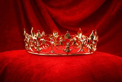 Royalty, monarch coronation or leadership conceptual idea with king gold crown with jewels on red velvet pillow