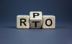 RPO vs RTO. Turned a cube and changed the word 'RTO - recovery time objective' to 'RPO - recovery point objective'. Business and RPO vs RTO concept. Beautiful grey background, copy space.