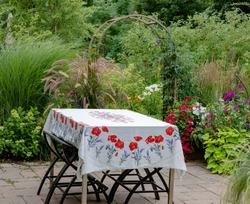 rred poppied tablecloth on a rectangular patio table with stainless steel base in an Impressionistic garden, with clematis climbing up the arbor