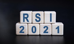 RSI 2021 text on wooden cubes on a black background with reflection.