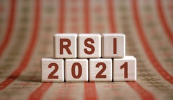 RSI 2021 text on wooden cubes on a monochrome background with reflection.