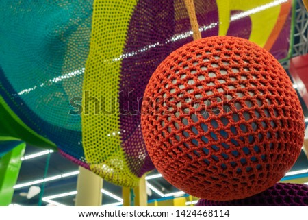 Rubber ball, covered with a red wicker mesh. Abstract texture of multi-colored woven fabrics. Creative vintage background #1424468114