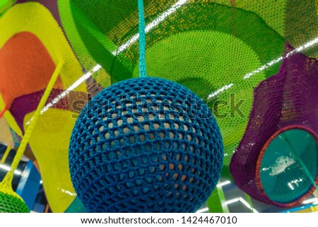 Rubber ball, covered with blue woven mesh. Abstract texture of multi-colored woven fabrics. Creative vintage background #1424467010