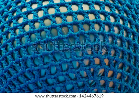 Rubber ball, covered with blue woven mesh. Abstract texture of multi-colored woven fabrics. Creative vintage background #1424467619