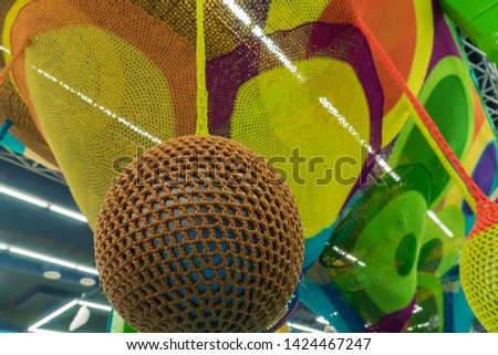 Rubber ball, covered with brown woven mesh. Abstract texture of multi-colored woven fabrics. Creative vintage background #1424467247