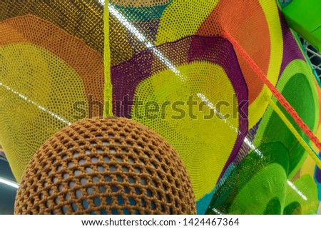 Rubber ball, covered with brown woven mesh. Abstract texture of multi-colored woven fabrics. Creative vintage background #1424467364