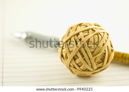 rubber band ball and pen on notebook paper with shallow depth of field