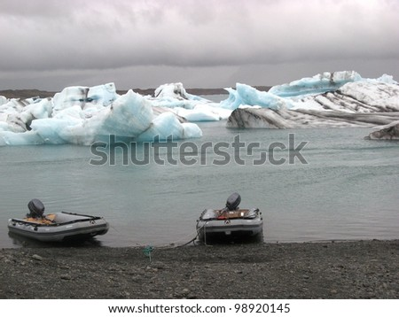 Rubber boats at the shore of Jokulsarlon glacier lake with icebergs under the threatening grey skies of Iceland