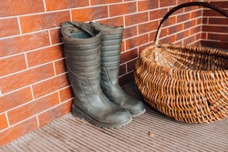 Rubber boots and a wicker basket on the terrace - mushroom picking season - a walk in the forest