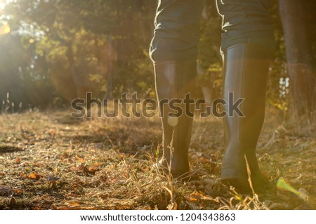 Rubber boots in backlight.. Hunter goes through his hunting grounds with rubber boots towards the setting sun. Stockfoto ©