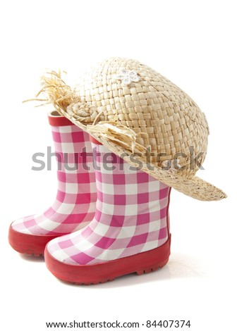 Rubber boots with straw head isolated over wiite