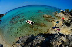 Rubber dinghy, anchored nearby small  lagoon, hidden among rocks, Sithonia, Greece, fisheye view from above