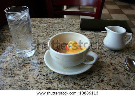rubber duck, floats in a cup of coffee in a restaurant